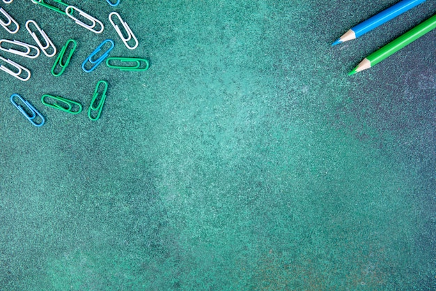 Widok z góry miejsca kopiowania biały zielony i niebieski spinacze z niebieskimi i jasnozielonymi ołówkami na zielonym tle