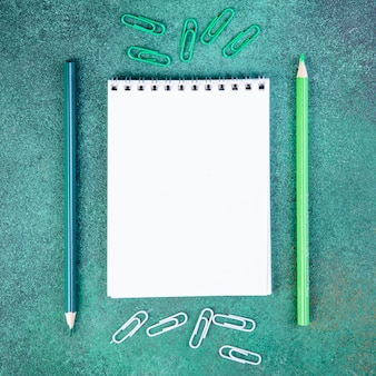 Widok z góry miejsca kopiowania jasnozielone i niebieskie ołówki ze spinaczami do papieru i notatnik na zielonym tle