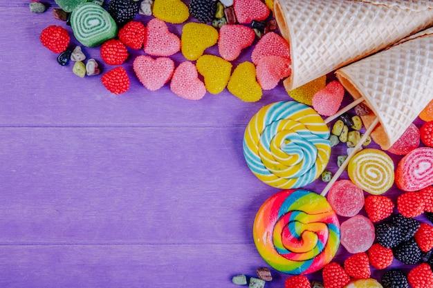 Widok z góry miejsca kopiowania wielobarwnej marmolady w różnych formach z kolorowymi soplami w rożki waflowe na fioletowym tle