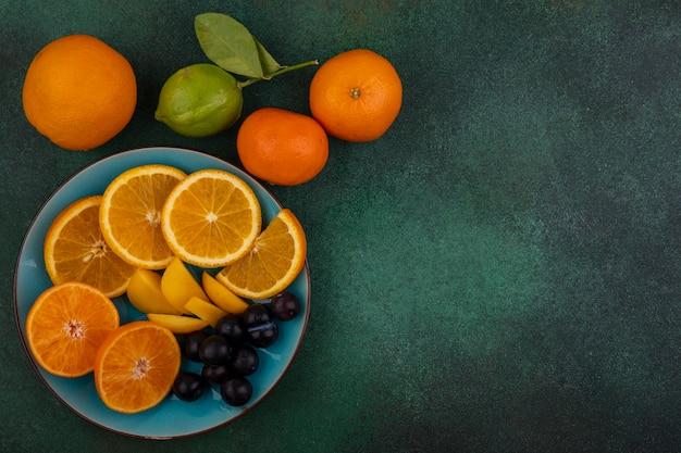 Widok z góry miejsca na kopię pomarańczowe plasterki czereśni na niebieskim talerzu z mandarynkami na zielonym tle
