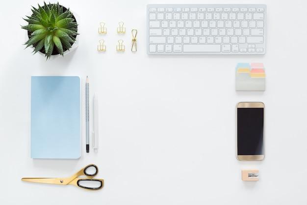 Widok z góry miejsca pracy firmy z klawiaturą komputera, notebookiem, zielonym kwiatem doniczkowym i telefonem komórkowym, leżał płasko.