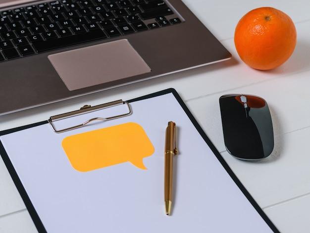 Widok z góry miejsca pracy projektanta z laptopem, tabletem, piórem i pomarańczą