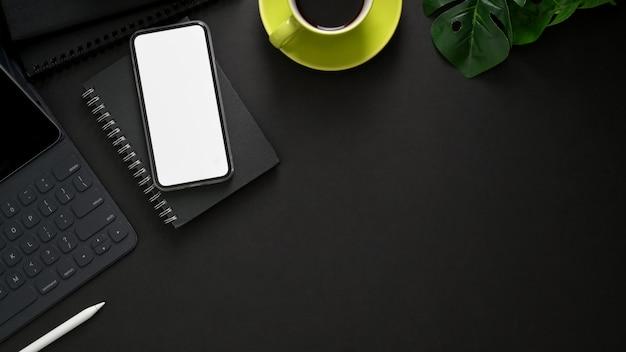 Widok z góry miejsca pracy z bezprzewodową klawiaturą, smartfonem, miejsca kopiowania, materiałów biurowych i filiżankę kawy na czarny stół