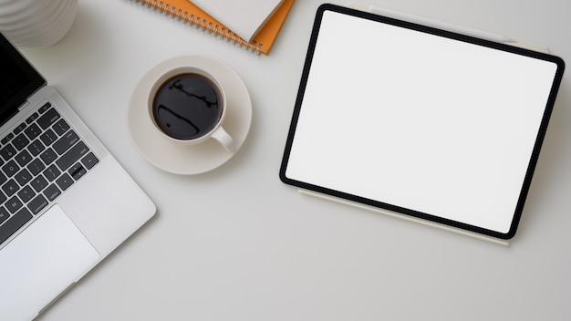 Widok z góry miejsca pracy z cyfrowym tabletem, laptopem i filiżanką kawy