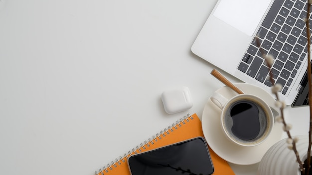Widok z góry miejsca pracy z laptopem, filiżanką kawy, urządzeniem bezprzewodowym, dekoracjami i miejsca kopiowania