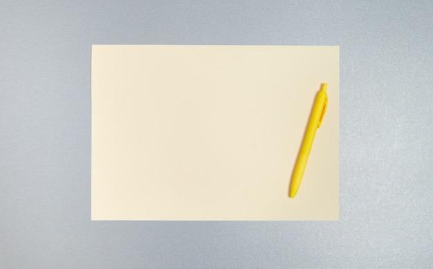 Widok z góry, miejsce na kopię, płaskie ułożenie żółtego długopisu i kartki papieru na szarej powierzchni. koncepcja biznesowa i biurowa