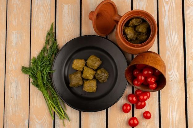 Widok z góry mielone mięso dolma wewnątrz czarnego talerza wraz z zieleniami i czerwonymi pomidorami cherry na drewnianym biurku
