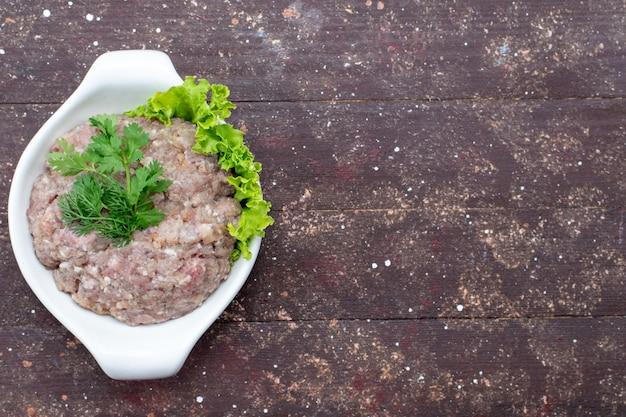 Widok z góry mielone surowe mięso z zieleniną wewnątrz płyty na brązowym biurku mięso surowe jedzenie posiłek zielony zdjęcie