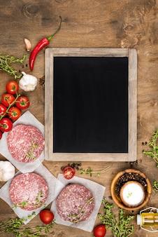Widok z góry mięsa z ziołami i tablicą