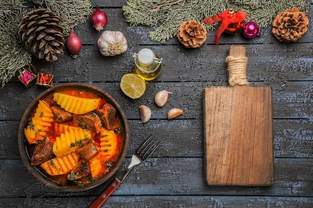 Widok z góry mięsna zupa z zieleniną i ziemniakami na ciemnym biurku