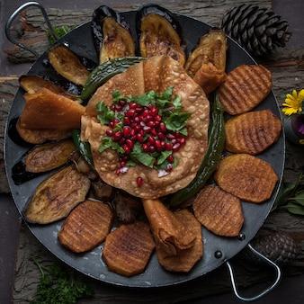 Widok z góry mięso z pieczonymi ziemniakami, bakłażanem, pomidorem, pieprzem i ozdobione granatem na drewnianej korze