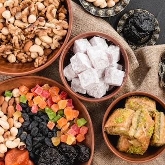 Widok z góry mieszanych orzechów; suszone owoce; lukum i baklava w glinianych misach na ramadan