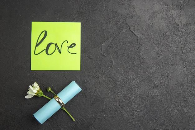 Widok z góry miłość napisana na zielonym karteczce pierścionek zaręczynowy kwiat zwinięty karteczka samoprzylepna na ciemnym tle miejsce kopiowania