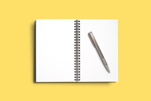 Widok z góry minimalna konstrukcja otwartego notesu z piórem na żółtym tle.