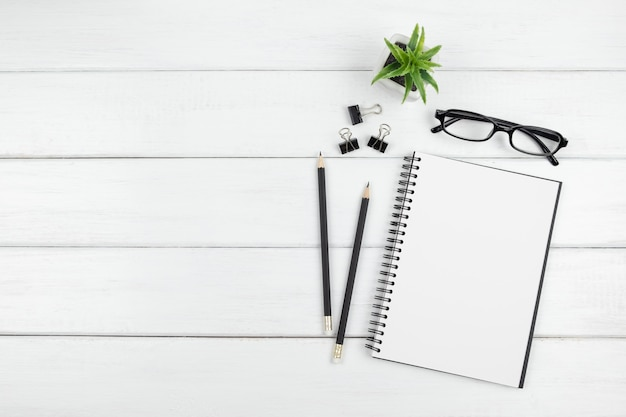 Widok z góry minimalnego biurka z otwartym pustym notatnikiem i artykułami biurowymi