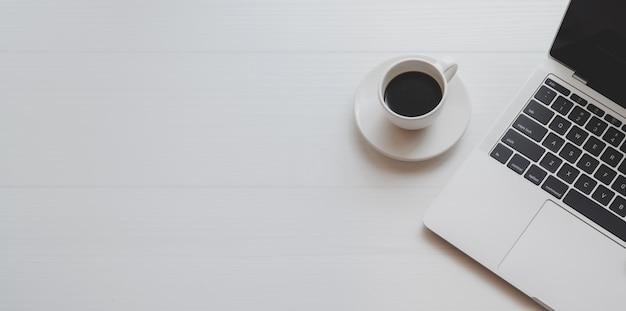 Widok z góry minimalnego miejsca pracy z laptopem i filiżanką kawy