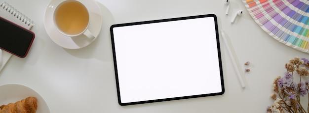 Widok z góry minimalnego stołu roboczego projektanta z tabletem, designerskimi materiałami eksploatacyjnymi i posiłkiem śniadaniowym
