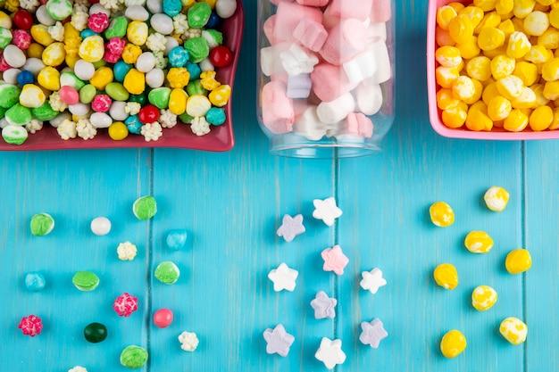 Widok z góry misek z różnych kolorowych cukierków i pianki rozrzucone ze szklanego słoika na niebieskim tle