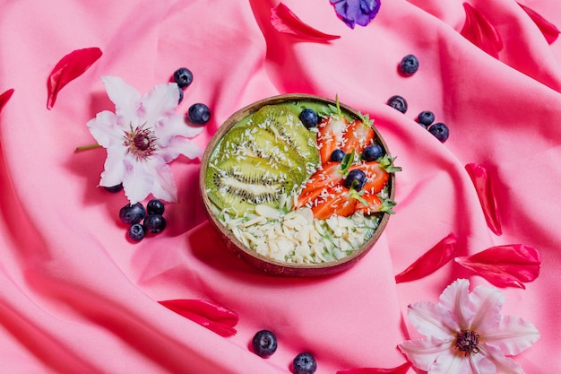 Widok z góry misek ze słodkimi owocowymi naczyniami umieszczonymi na różowym materiale
