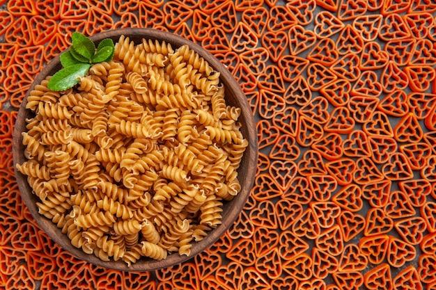 Widok z góry miska makaronu spirali na włoskim makaronie serca na ciemnym stole