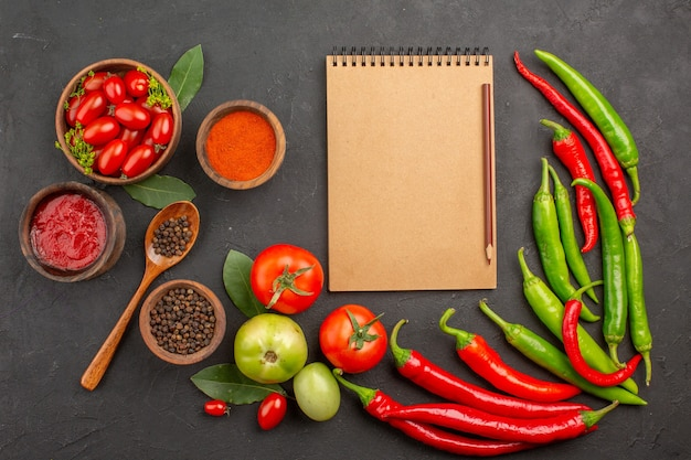 Widok z góry miska pomidorków koktajlowych gorąca czerwona i zielona papryka i pomidory liście laurowe miski keczupu czerwonej papryki i czarnego pieprzu oraz notatnik na ziemi