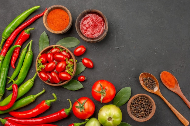 Widok z góry miska pomidorków koktajlowych gorąca czerwona i zielona papryka liście laurowe przyprawy w drewnianych łyżkach miski keczupu ostra czerwona papryka w proszku i czarny pieprz i pomidor na czarno
