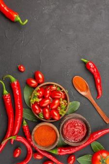 Widok z góry miska pomidorków koktajlowych gorąca czerwona papryka drewniana łyżka liście laurowe miski keczupu i ostrej papryki w proszku i pomidor na dnie czarnej ziemi