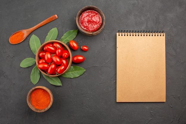 Widok z góry miska pomidorków koktajlowych, liście laurowe, drewniana łyżka i miski keczupu i ostrej papryki oraz notatnik na czarnym stole