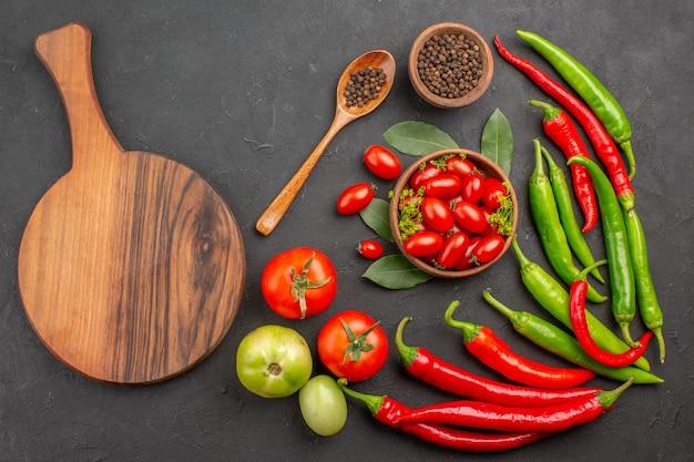 Widok z góry miska pomidorków koktajlowych ostra czerwona papryka czarny pieprz w drewnianej łyżce miska czarnego pieprzu i owalna deska do krojenia na czarnym tle