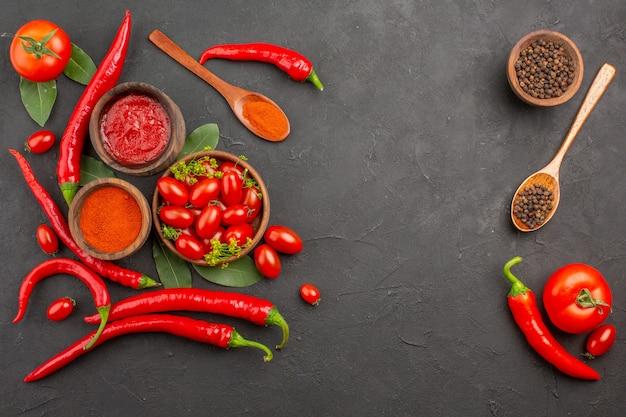 Widok z góry miska pomidorków koktajlowych ostra czerwona papryka czarny pieprz w drewnianej łyżce miski keczupu czarnego pieprzu i czerwonej papryki mielonej na czarnej ziemi