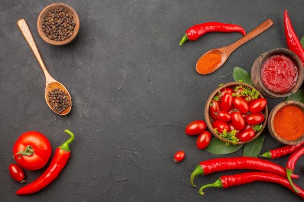 Widok z góry miska pomidorków koktajlowych ostra czerwona papryka czarny pieprz w drewnianej łyżce miski keczupu czarnego pieprzu i czerwonej papryki w proszku na czarnym stole