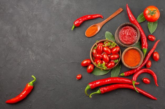 Widok z góry miska pomidorów wiśniowych gorąca czerwona papryka drewniana łyżka liście laurowe miski keczupu i ostrej papryki w proszku i pomidor na czarnej ziemi