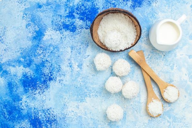 Widok z góry miska w proszku kokosowym i kulki kokosowe na niebieskim białym tle