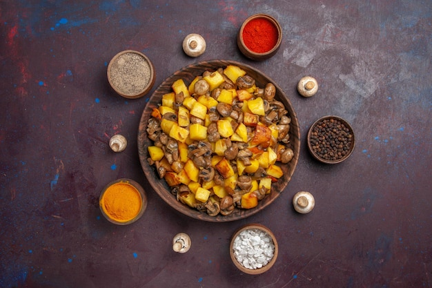 Widok z góry miska z jedzeniem i przyprawami miska z ziemniakami i grzybami oraz kolorowymi przyprawami