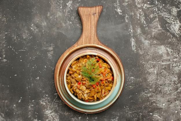 Widok z góry miska zielonej fasoli miska zielonej fasoli z pomidorami na tacy i drewniana deska do krojenia na ciemnej powierzchni