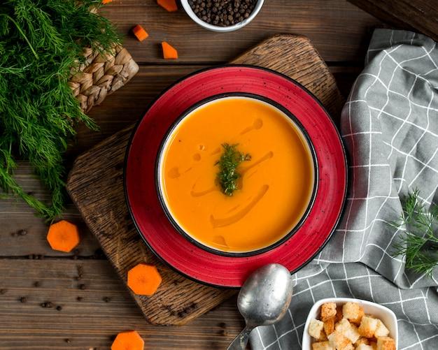Widok z góry miska zupy marchewkowej przyozdobionym z koperkiem