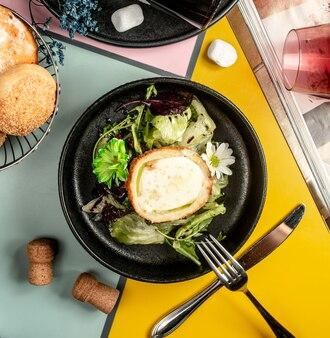 Widok z góry miski panierowanego kurczaka wypełnionego serem i sałatą