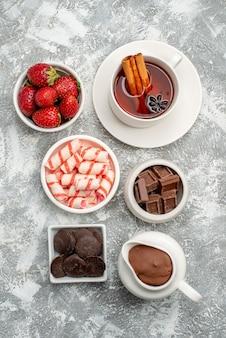 Widok z góry miski z cukierkami kakaowymi truskawki czekoladki herbata z cynamonem na szaro-białym stole