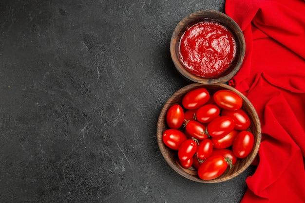 Widok z góry miski z pomidorkami cherry i keczupem i czerwonym ręcznikiem na ciemnym tle