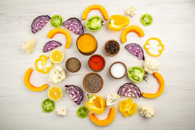 Widok z góry miski z przyprawami kurkuma pieprz czarny sól pieprz czerwony proszek pokrojone warzywa na białej powierzchni