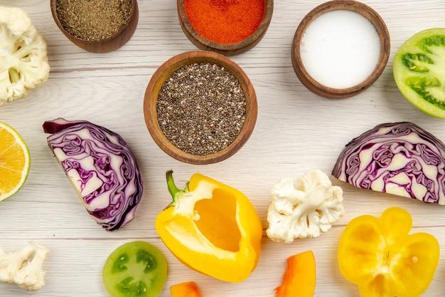 Widok z góry miski z przyprawami pokroić paprykę kalafior pokroić czerwoną kapustę pokroić zielone pomidory na białym stole