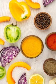 Widok z góry miski z przyprawami pokroić paprykę pokroić dyni pokroić czerwoną kapustę pokroić zielone pomidory pokroić cytrynę na białym stole