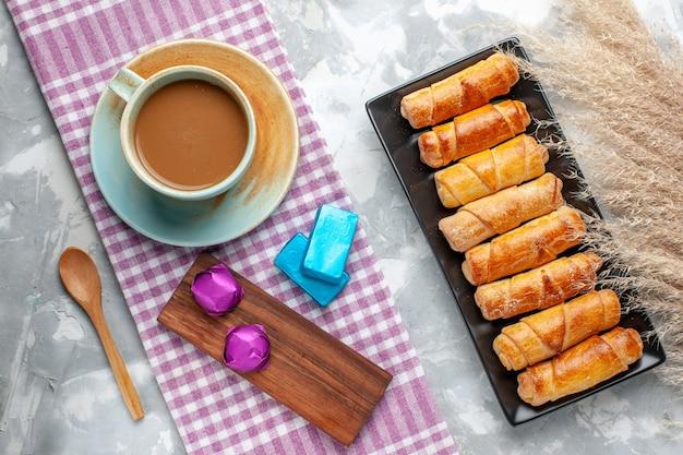 Widok z góry mleczna kawa z bransoletkami na szarym biurku ciasto biszkoptowe słodki cukier