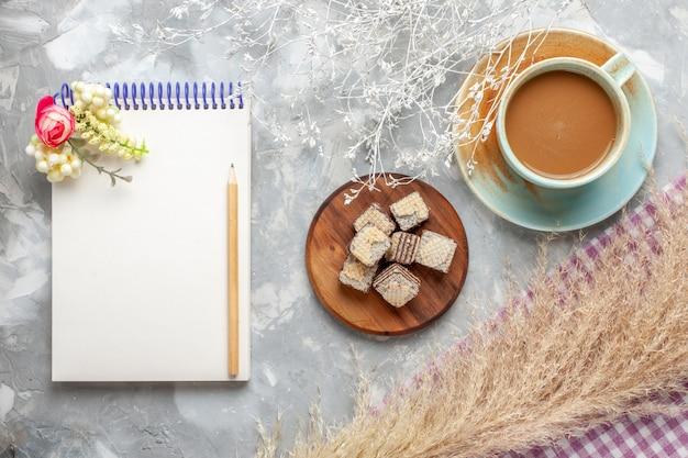 Widok z góry mleczna kawa z czekoladowymi goframi i notatnikiem na jasnym tle czekoladowe ciasteczko słodki cukier