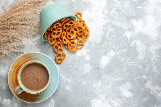 Widok z góry mleczna kawa z krakersami na jasnym tle ostry napój kawa kolorowe zdjęcie