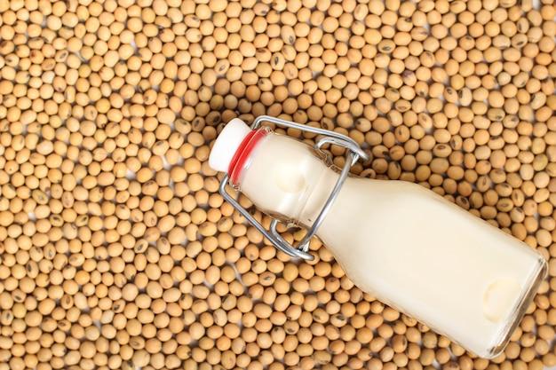 Widok z góry mleko sojowe w butelce i ziarna na drewnianym stole i rustykalne tło kuchnia. koncepcja alternatywnego mleka. koncepcja produktu sojowego