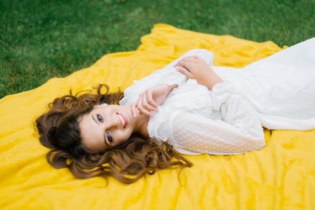 Widok z góry młoda kobieta na pikniku, leżąc na kocu. jest szczęśliwa i uśmiecha się olśniewająco