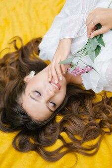 Widok z góry młoda kobieta na pikniku, leżąc na kocu. jest szczęśliwa, uśmiecha się olśniewająco śnieżnobiałym uśmiechem i trzyma w dłoniach kwiat