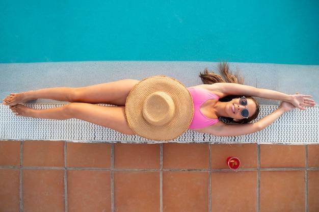 Widok z góry młoda kobieta relaksująca się przy basenie?