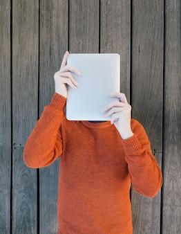 Widok z góry młodego człowieka czytającego na swoim tablecie, nie widząc twarzy na niektórych drewnianych deskach iz pomarańczowym dżersejem